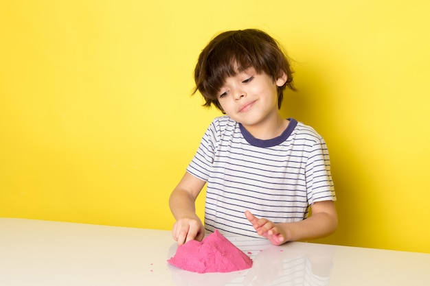 A front view cute adorable boy in striped t-shirt playing with colorful kinetic sand