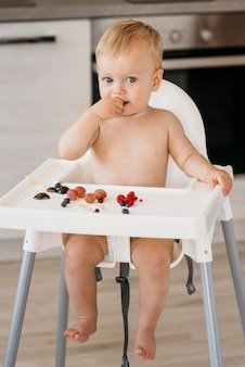Вид спереди милый ребенок в стульчике, выбирающий, какие фрукты съесть
