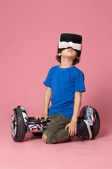 A front view cute boy in blue t-shirt playing vr on segway on the pink floor