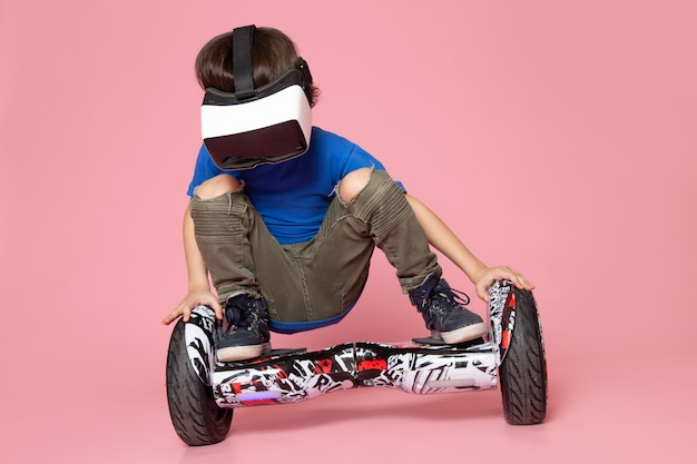 A front view cute boy in blue t-shirt playing vr on segway on the pink space