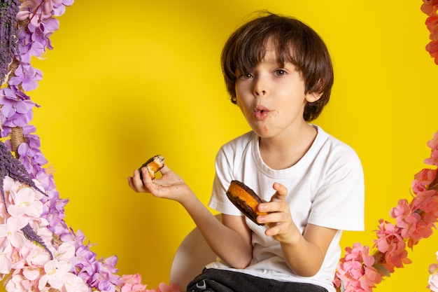 A front view cute boy eating choco donuts in white t-shirt on the yellow desk