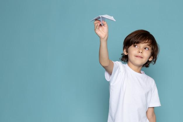 Вид спереди милый мальчик держит бумажный самолетик в белой футболке на синем полу