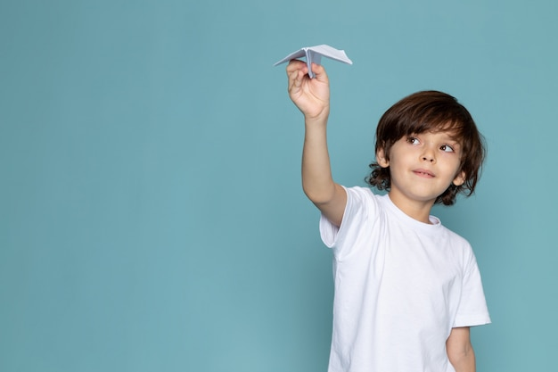 Front view cute boy holding paper plane in white t-shirt on the blue floor