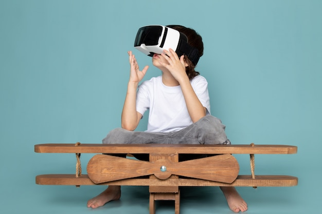 Front view cute boy playing vr goggles in white t-shirt on the blue