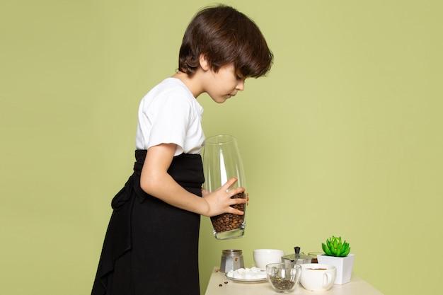 Un ragazzo sveglio di vista frontale che prepara la bevanda del caffè sullo scrittorio color pietra
