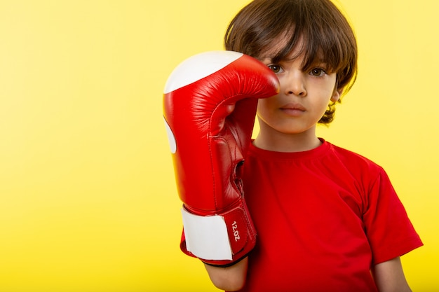 A front view cute boy in red boxing gloves and in red t-shirt on the yellow wall