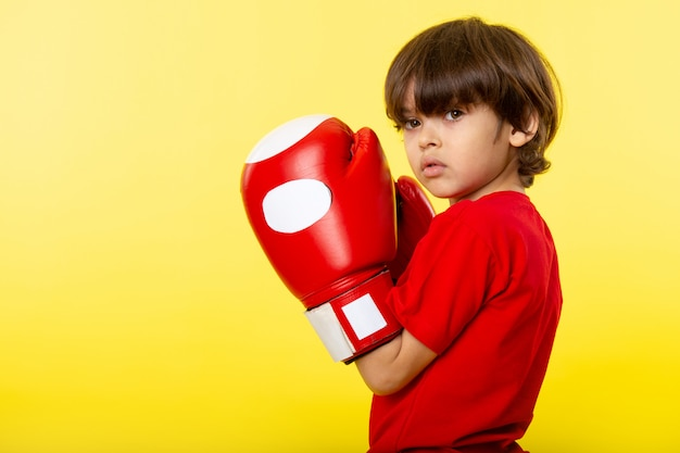 A front view cute boy in red boxing gloves and red t-shirt on the yellow wall