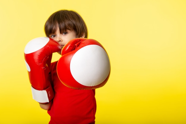 A front view cute boy in red t-shirt and with red boxing gloves on the yellow wall