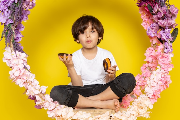 A front view cute boy in white t-shirt eating donuts on the flower made stand on the yellow space