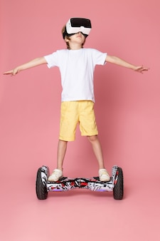 A front view cute boy in white t-shirt and orange shorts riding segway on the pink space