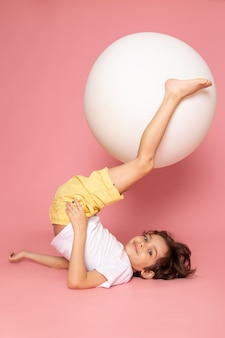 A front view cute boy in white t-shirt playing with round white ball on the pink floor