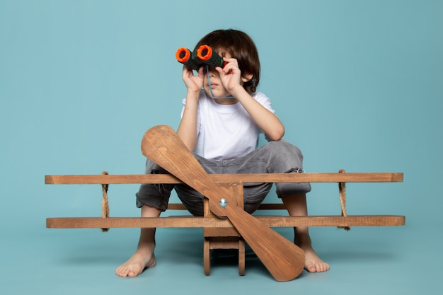 Front view cute boy in white t-shirt using binoculars on blue