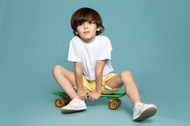 A front view cute boy in white t-shirt and yellow shorts riding green skateboard on the blue space