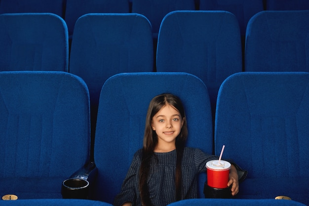 Front view of cute brunette female kid looking at camera and smiling while enjoying film in cinema