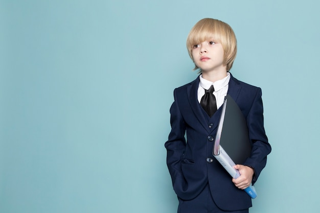 A front view cute business boy in blue classic suit holding black folder business work fashion