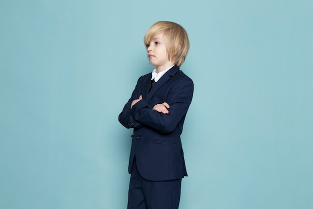 A front view cute business boy in blue classic suit posing business work fashion