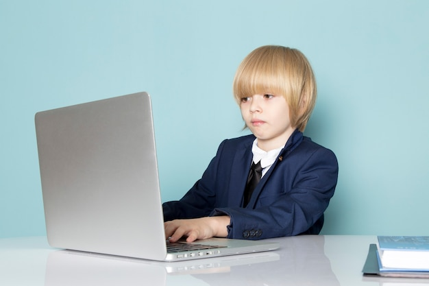 A front view cute business boy in blue classic suit posing in front of silver laptop working business work fashion
