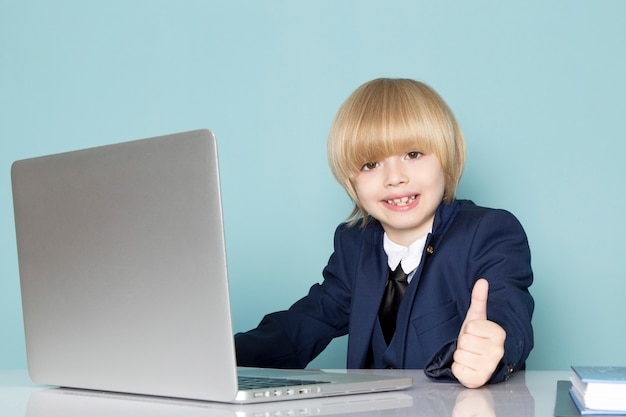 A front view cute business boy in blue classic suit posing in front of silver laptop working smiling business work fashion