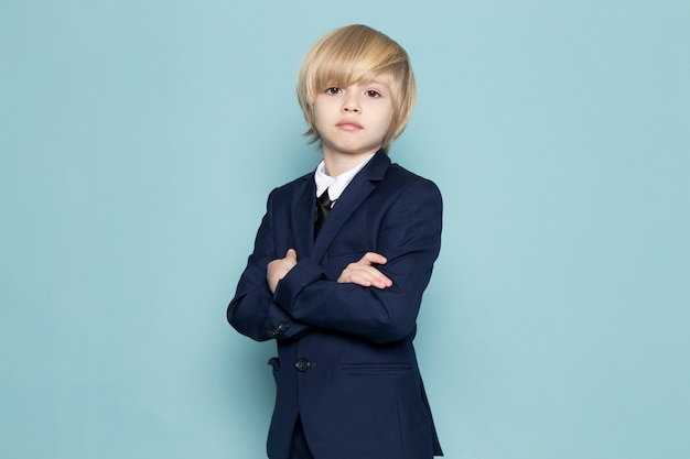A front view cute business boy in blue classic suit posing looking into the camera business work fashion