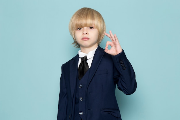A front view cute business boy in blue classic suit posing showing alright sign business work fashion