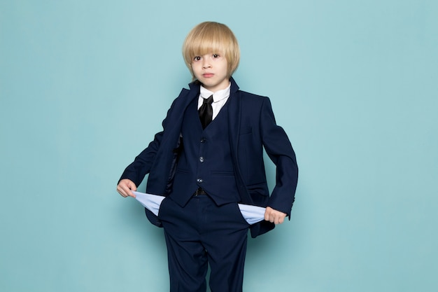 A front view cute business boy in blue classic suit posing showing his pockets business work fashion