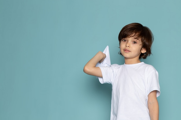 Front view cute child adorable sweet holding paper plane on the blue desk