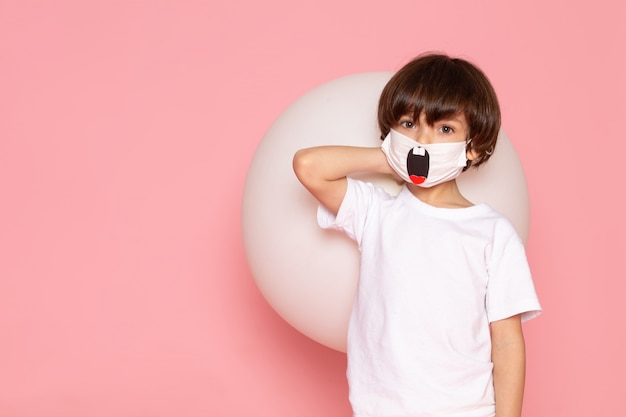 A front view cute child boy in white t-shirt and funny mask holding white ball on the pink desk