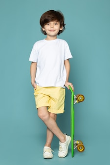 A front view cute child boy in white t-shirt and yellow jeans holding green skateboard on the blue floor