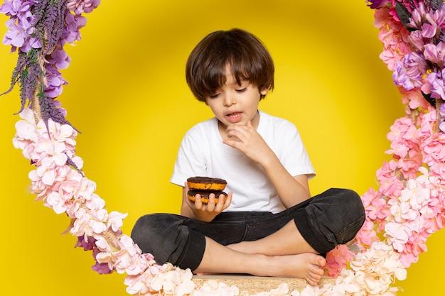 Un bambino sveglio di vista frontale che mangia le ciambelle al cioccolato in maglietta bianca sul pavimento giallo