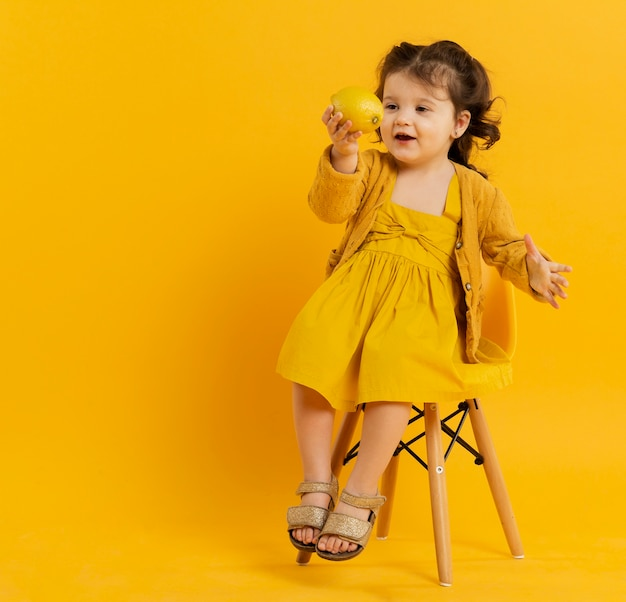 Front view of cute child posing while holding lemon