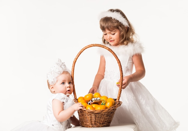 Front view of cute children standing next to basket with oranges and sweets.