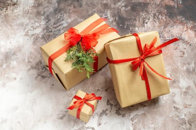 Vista frontale simpatici regali di natale legati con fiocchi rossi su sfondo chiaro