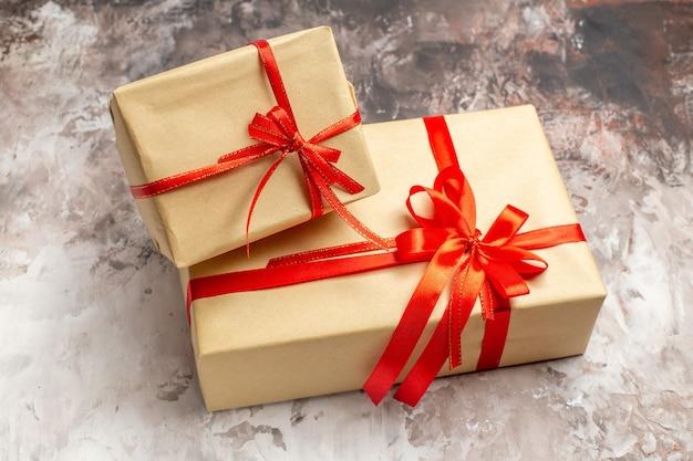明るい背景に赤い弓で結ばれた正面のかわいいクリスマス プレゼント