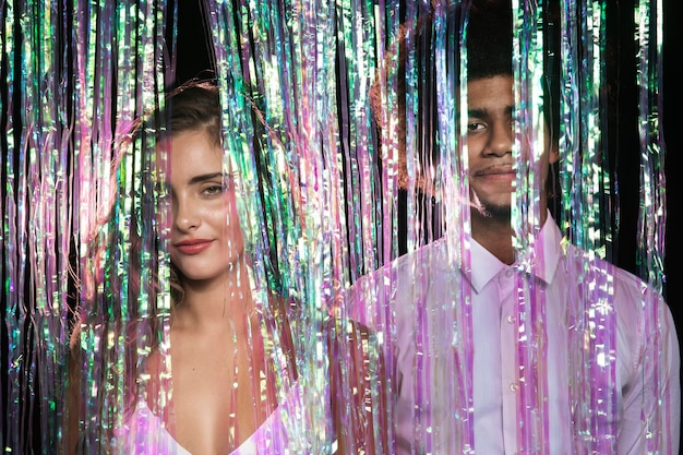Front view cute couple standing in a curtain of sparkles