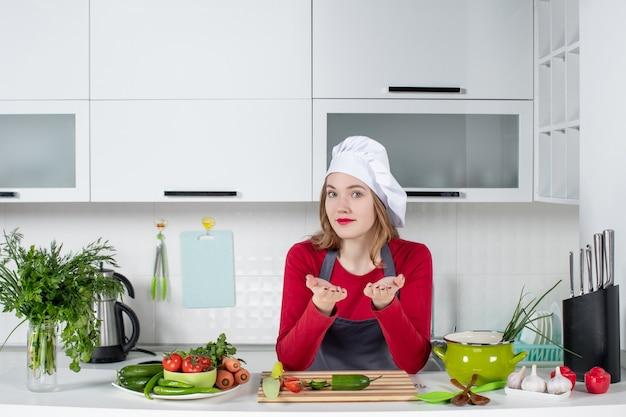 Cuoco unico femminile sveglio di vista frontale in cappello del cuoco che sta nella cucina