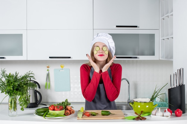 Front view cute female chef in uniform putting cucumber slices on her face