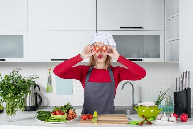 Cuoca carina vista frontale in grembiule che mette i pomodori davanti ai suoi occhi