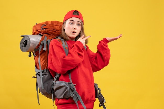 右指で指しているバックパックと正面図かわいい女性旅行者