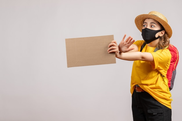 Front view of cute female traveller with backpack holding cardboard on grey isolated wall