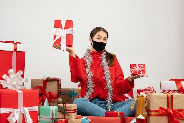 선물 주위에 앉아 양손에 선물을 들고 검은 마스크와 전면보기 귀여운 소녀