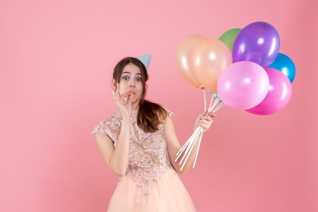 おいしい看板を作る風船を保持しているパーティーキャップと正面図かわいい女の子