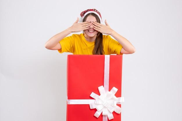 큰 크리스마스 선물 뒤에 서있는 그녀의 눈 재치 손을 덮고 산타 모자와 전면보기 귀여운 소녀
