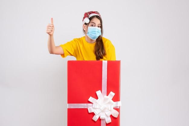 큰 크리스마스 선물 뒤에 서 가입 엄지 손가락을 만드는 산타 모자와 전면보기 귀여운 소녀