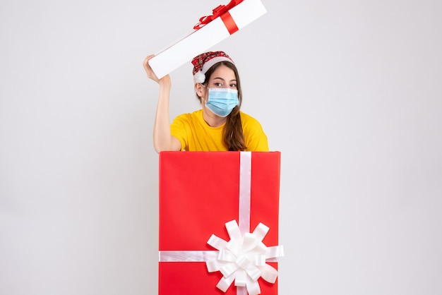 Front view cute girl with santa hat and medical mask standing behind big xmas gift