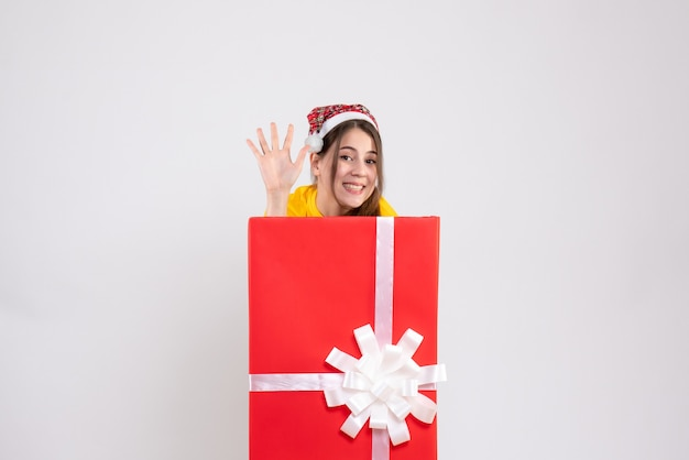 Вид спереди милая девушка в новогодней шапке поздоровается за большим рождественским подарком