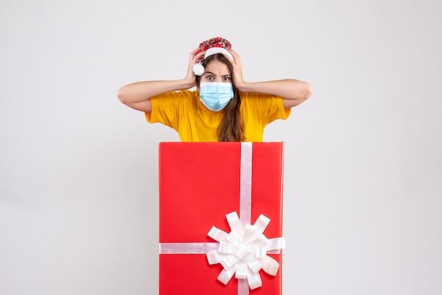 큰 크리스마스 선물 뒤에 서있는 그녀의 머리 모자를 들고 산타와 전면보기 귀여운 소녀