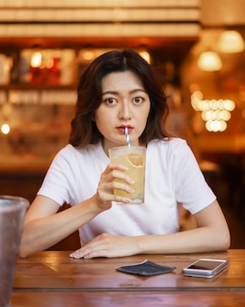 Front view of cute japanese girl drinking lemonade