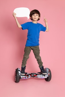 A front view cute kid in blue t-shirt and khaki trousers riding segway on the pink space
