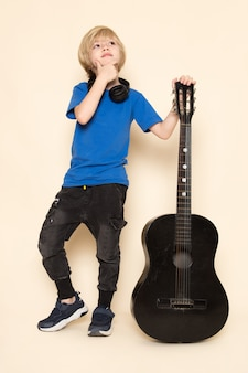 A front view cute little boy in blue t-shirt with black headphones holding black guitar