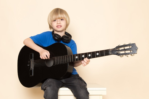 A front view cute little boy in blue t-shirt with black headphones playing black guitar